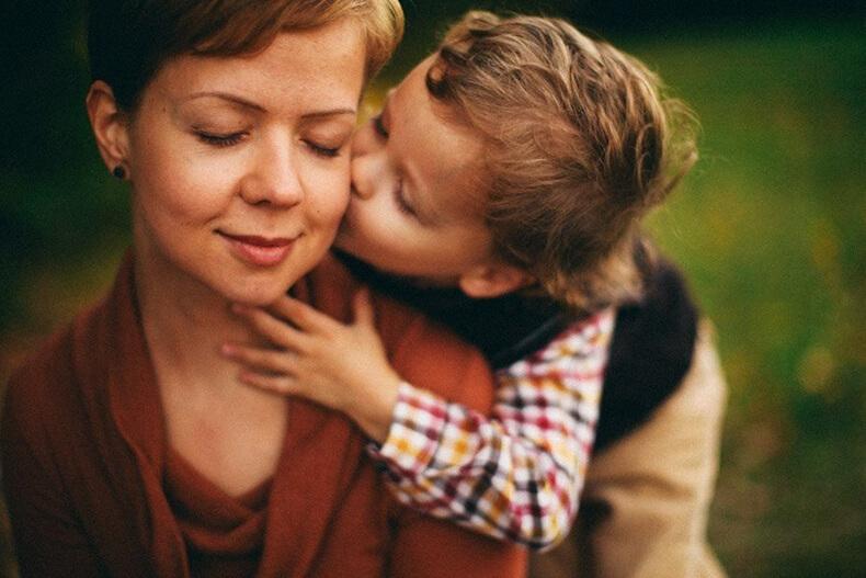 Мама с сыном на кухне целуются