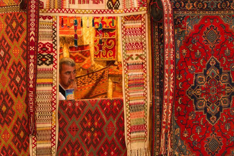 Продавец на фоне красных ковров в Узбекистане