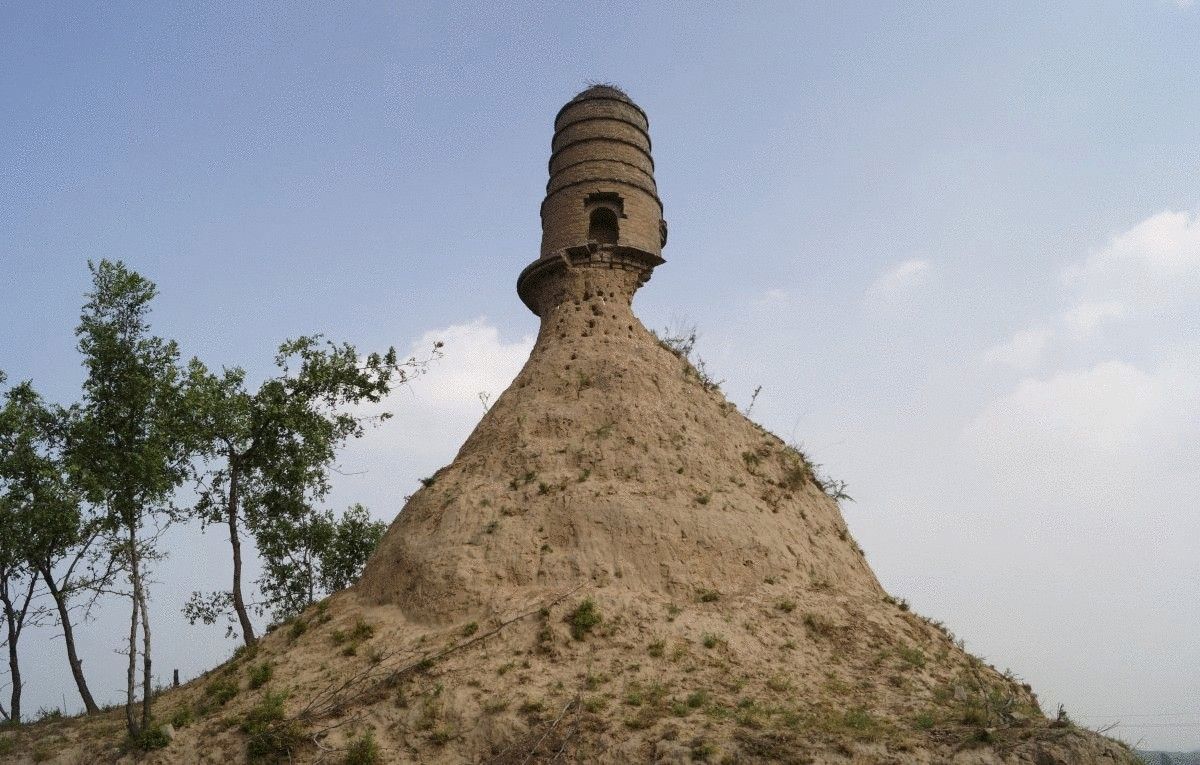 an-ancient-tower-is-seen-balancing-on-top-of-a-dirt-hill-with-its-base-almost-entirely-eroded-along-a-grassland-in-shanxi-province-china-in-july